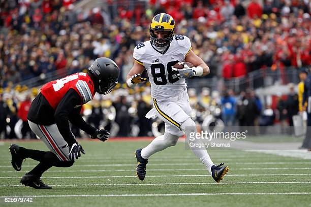Jake Butt of the Michigan Wolverines runs after catching a pass in overtime against the Ohio State Buckeyes at Ohio Stadium on November 26 2016 in...