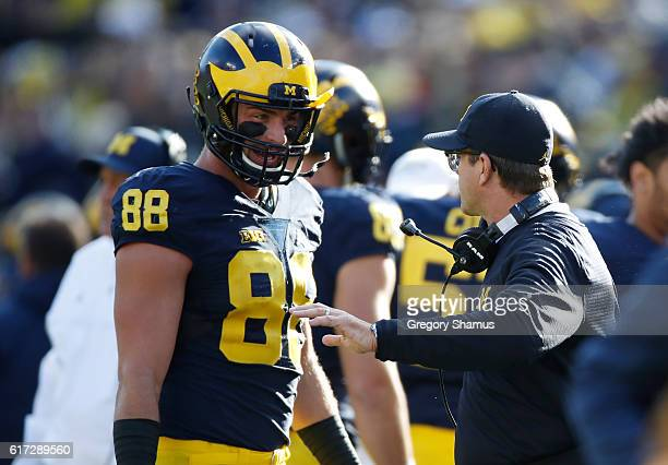 Jake Butt of the Michigan Wolverines talks with head coach Jim Harbaugh while playing the Illinois Fighting Illini on October 22 2016 at Michigan...