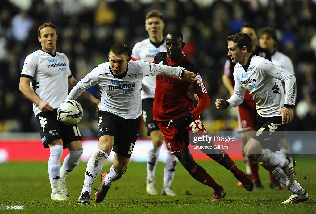 Jake Buxton of Derby County battles with Albert Adomah of Bristol City during the npower Championship match between Derby County and Bristol City at Pride Park Stadium on March 29, 2013 in Derby, England.