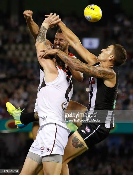 Jake Carlisle and Jarryn Geary of the Saints compete for the ball with Jesse White of the Magpies during the 2017 AFL round 04 match between the...