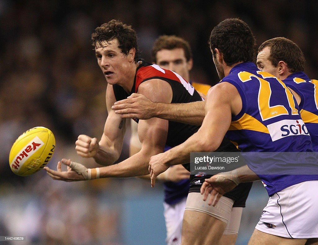 Jake Carlisle of the Bombers handballs the ball during the round seven AFL match between the Essendon Bombers and the West Coast Eagles at Etihad Stadium on May 12, 2012 in Melbourne, Australia.