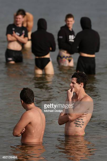 Jake Carlisle of the Bombers is seen in the water in front of Magpies players during a Collingwood Magpies AFL recovery session at St Kilda Beach on...