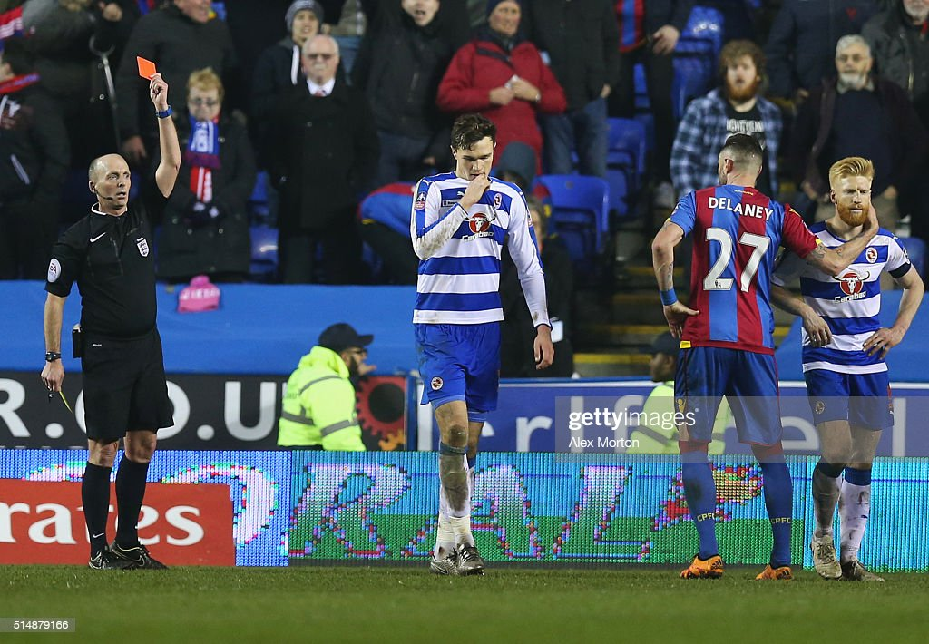 Jake Cooper of Reading (2L) is shown a red card by referee <a gi-track='captionPersonalityLinkClicked' href=/galleries/search?phrase=Mike+Dean+-+Referee&family=editorial&specificpeople=4517613 ng-click='$event.stopPropagation()'>Mike Dean</a> and is sent off during the Emirates FA Cup sixth round match between Reading and Crystal Palace at Madejski Stadium on March 11, 2016 in Reading, England.