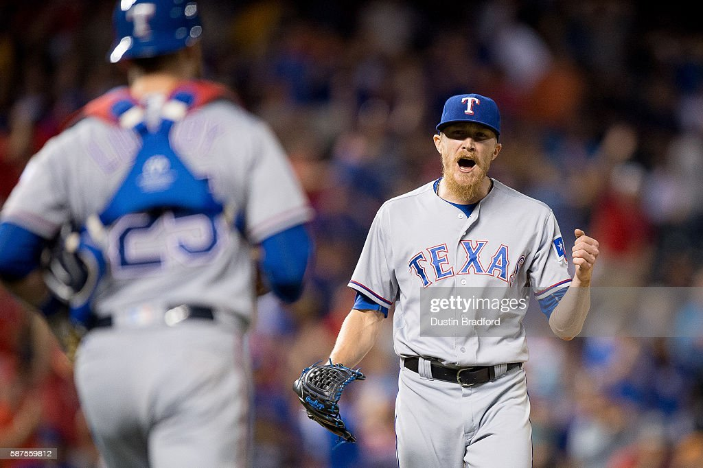 Jake Diekman #41 and Jonathan Lucroy #25 of the Texas Rangers celebrate after closing out a 4-3 win over the Colorado Rockies at Coors Field on August 8, 2016 in Denver, Colorado.