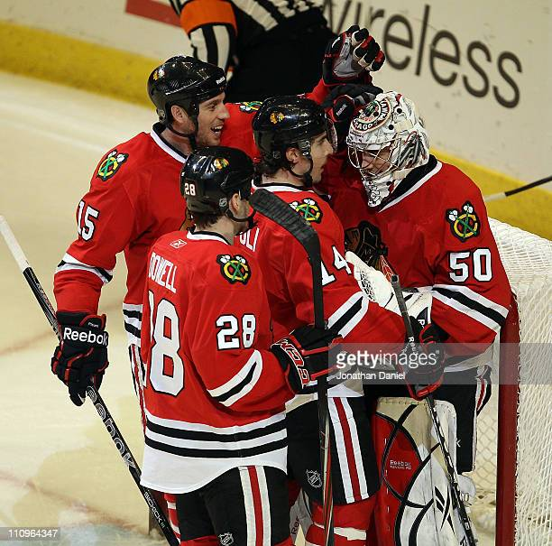 Jake Dowell Fernando Pisani and Chris Campoli of the Chicago Blackhawks congratulate Corey Crawford after a win over the Florida Panthers at the...