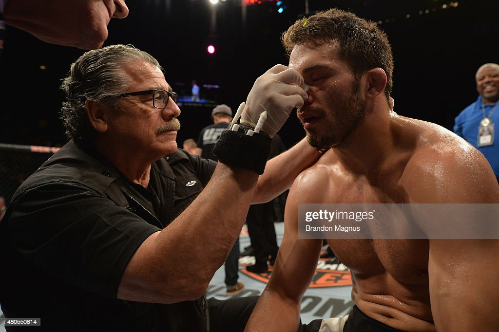 Jake Ellenberger is inspected by a cutman after losing to Stephen Thompson in their welterweight bout during the Ultimate Fighter Finale inside MGM Grand Garden Arena on July 12, 2015 in Las Vegas, Nevada.