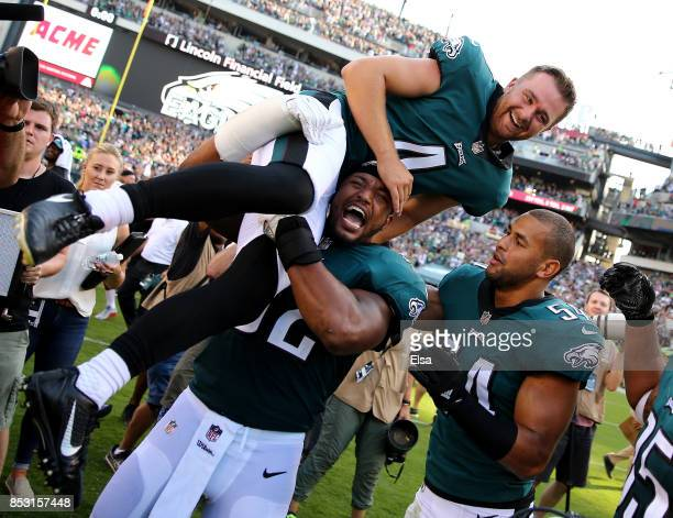 Jake Elliott of the Philadelphia Eagles is picked up by teammates Najee Goode and Kamu GrugierHill after Elliott kicked the game winning field goal...