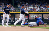 Jake Elmore of the Milwaukee Brewers attempts to turn a double play past Willson Contreras of the Chicago Cubs at Miller Park on July 24 2016 in...