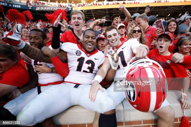 Jake Fromm and Jonathan Ledbetter of the Georgia Bulldogs celebrate with fans after a game against the Tennessee Volunteers at Neyland Stadium on...