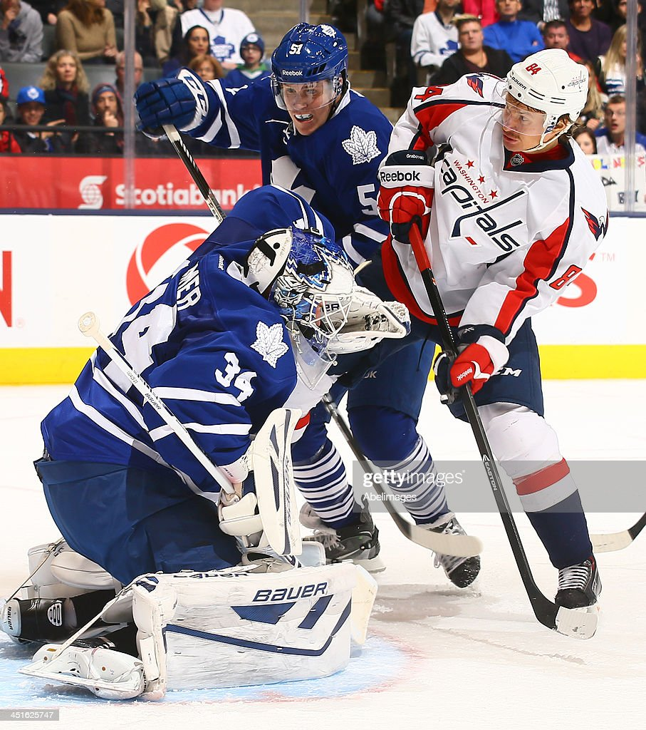 Jake Gardiner #51 and James Reimer #34 of the Toronto Maple Leafs stop Mikhail Grabovski #84 of the Washington Capitals during NHL action at the Air Canada Centre November 23, 2013 in Toronto, Ontario, Canada.