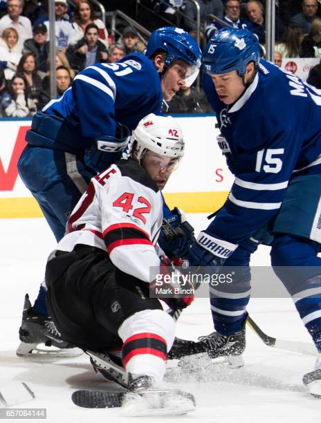 Jake Gardiner and Matt Martin of the Toronto Maple Leafs battle with John Quenneville of the New Jersey Devils during the second period at the Air...