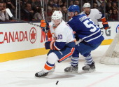 Jake Gardiner of the Toronto Maple Leafs battles for the puck with Keith Aucoin of the New York Islanders during NHL action at the Air Canada Centre...