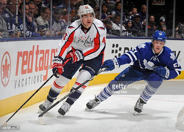 Jake Gardiner of the Toronto Maple Leafs battles for the puck with Tom Wilson of the Washington Capitals during NHL game action November 23 2013 at...