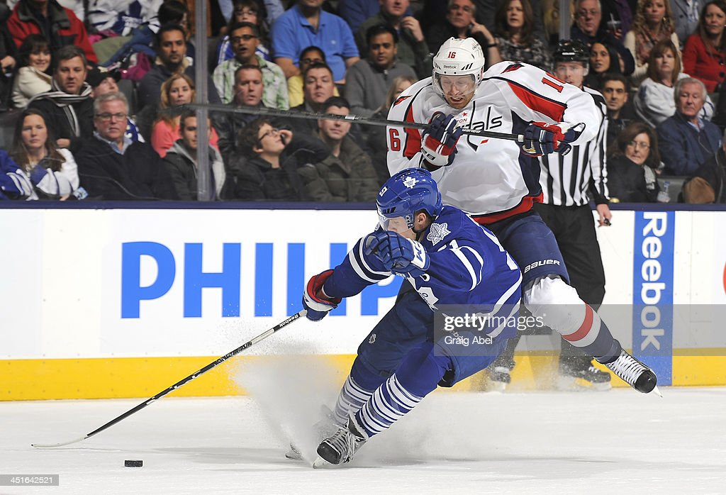 Jake Gardiner #51 of the Toronto Maple Leafs checks Eric Fehr #16 of the Washington Capitals during NHL game action November 23, 2013 at the Air Canada Centre in Toronto, Ontario, Canada.