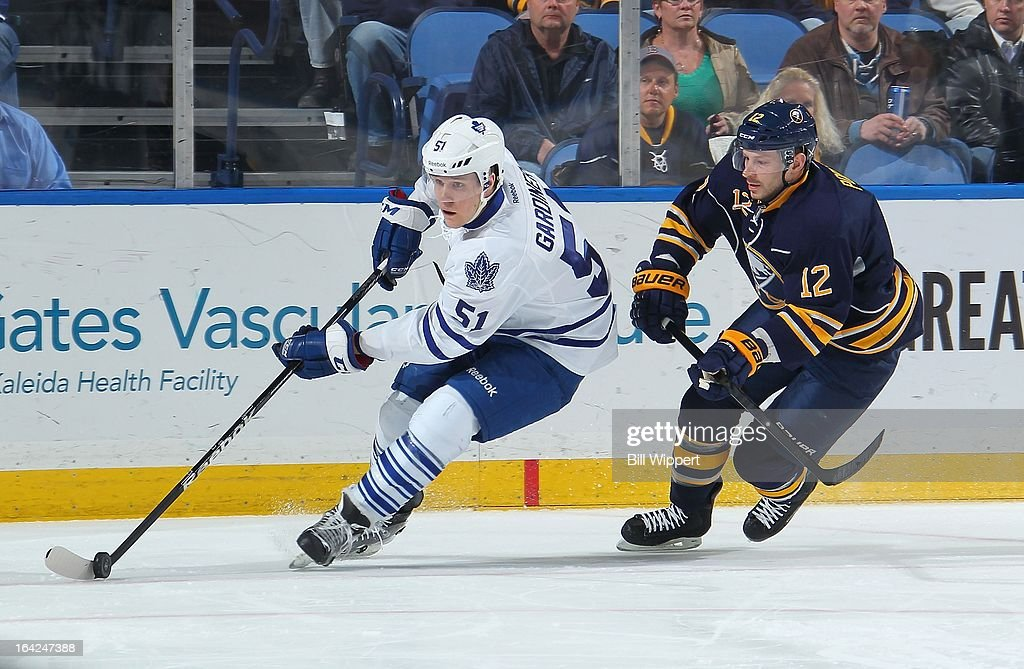 Jake Gardiner #51 of the Toronto Maple Leafs controls the puck against Kevin Porter #12 of the Buffalo Sabres on March 21, 2013 at the First Niagara Center in Buffalo, New York.