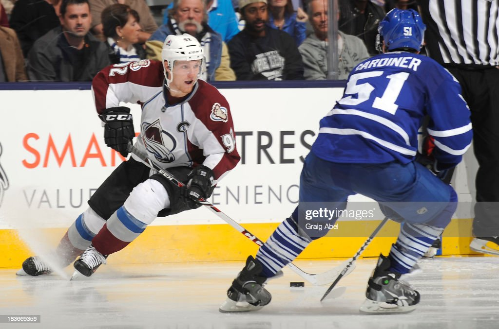<a gi-track='captionPersonalityLinkClicked' href=/galleries/search?phrase=Jake+Gardiner&family=editorial&specificpeople=4884939 ng-click='$event.stopPropagation()'>Jake Gardiner</a> #51 of the Toronto Maple Leafs defends as <a gi-track='captionPersonalityLinkClicked' href=/galleries/search?phrase=Gabriel+Landeskog&family=editorial&specificpeople=6590816 ng-click='$event.stopPropagation()'>Gabriel Landeskog</a> #92 of the Colorado Avalanche looks to pass the puck during NHL game action October 8, 2013 at Air Canada Centre in Toronto, Ontario, Canada.
