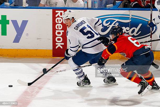 Jake Gardiner of the Toronto Maple Leafs skates with the puck against Vincent Trocheck of the Florida Panthers at the BBT Center on April 10 2014 in...