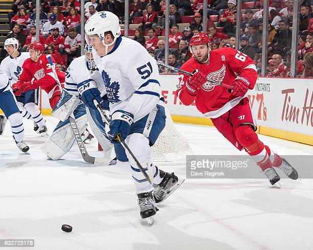 Jake Gardiner of the Toronto Maple Leafs skates with the puck around the net followed by Thomas Vanek of the Detroit Red Wings during an NHL game at...