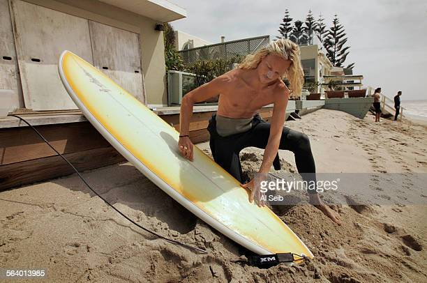MALIBU CA Jake Grace 28 year old from Malibu waxes his board to take advantage of the big waves on the back deck of his friends boarded up house in...