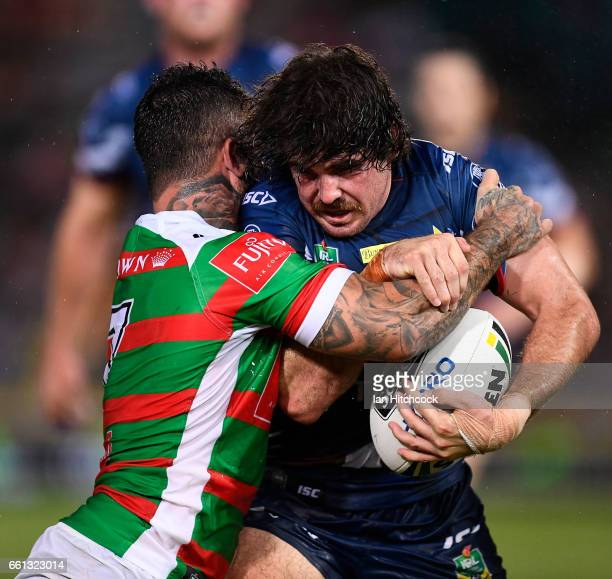 Jake Granville of the Cowboys is tackled by Adam Reynolds of the Rabbitohs during the round five NRL match between the North Queensland Cowboys and...