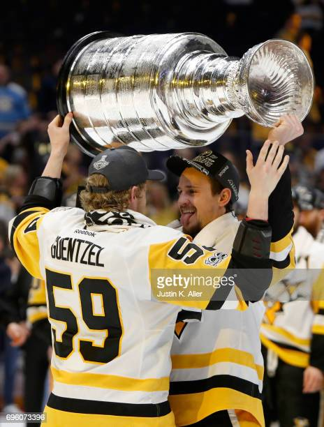 Jake Guentzel and Josh Archibald of the Pittsburgh Penguins celebrate with the Stanley Cup Trophy after defeating the Nashville Predators 20 in Game...