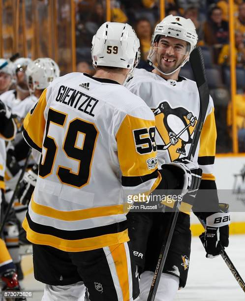 Jake Guentzel celebrates his goal with Justin Schultz of the Pittsburgh Penguins against the Nashville Predators during an NHL game at Bridgestone...