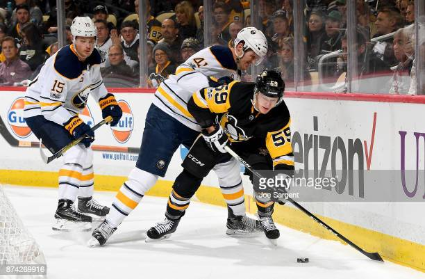 Jake Guentzel of the Pittsburgh Penguins and Justin Falk of the Buffalo Sabres battle in the corner at PPG Paints Arena on November 14 2017 in...