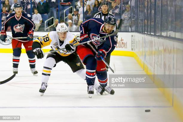 Jake Guentzel of the Pittsburgh Penguins attempts to steal the puck from Nick Foligno of the Columbus Blue Jackets in Game Three of the Eastern...