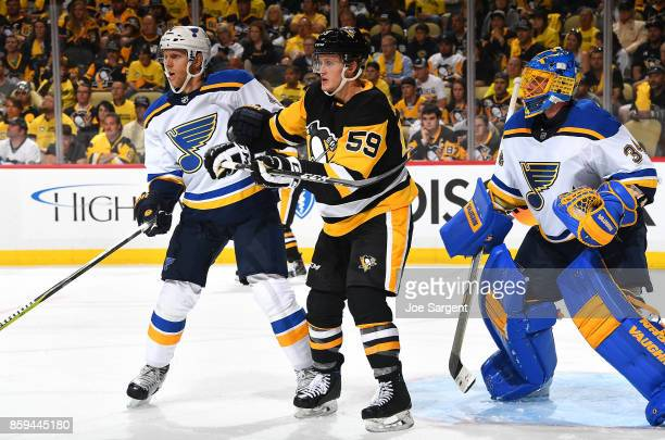 Jake Guentzel of the Pittsburgh Penguins battles for position between Carl Gunnarsson and Jake Allen of the St Louis Blues at PPG Paints Arena on...