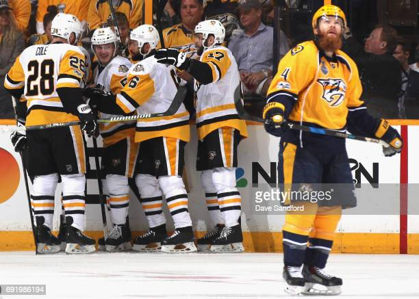 Jake Guentzel of the Pittsburgh Penguins celebrates his goal with teammates as Ryan Ellis of the Nashville Predators skates by during the first...