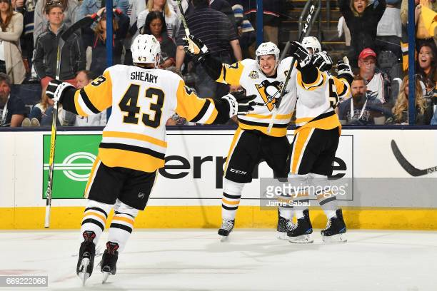 Jake Guentzel of the Pittsburgh Penguins celebrates his overtime goal with teammates Sidney Crosby and Conor Sheary of the Pittsburgh Penguins in...