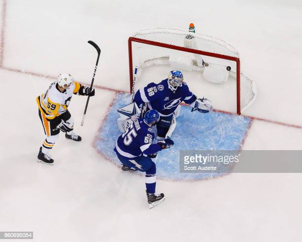 Jake Guentzel of the Pittsburgh Penguins deflects the puck for a goal against goalie Andrei Vasilevskiy and Braydon Coburn of the Tampa Bay Lightning...