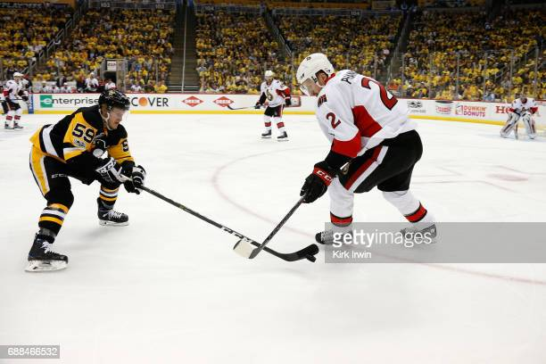Jake Guentzel of the Pittsburgh Penguins fights for the puck against Dion Phaneuf of the Ottawa Senators during the first period in Game Seven of the...