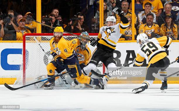 Jake Guentzel of the Pittsburgh Penguins fires a shot as Ryan Ellis of the Nashville Predators slides to make the block while Olli Maatta of the...