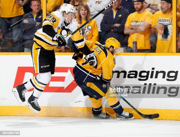 Jake Guentzel of the Pittsburgh Penguins goes airborne as Ryan Ellis of the Nashville Predators works the puck off the boards during Game Six of the...