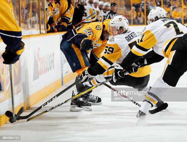 Jake Guentzel of the Pittsburgh Penguins goes for the puck along the boards during Game Six of the 2017 NHL Stanley Cup Final at Bridgestone Arena on...