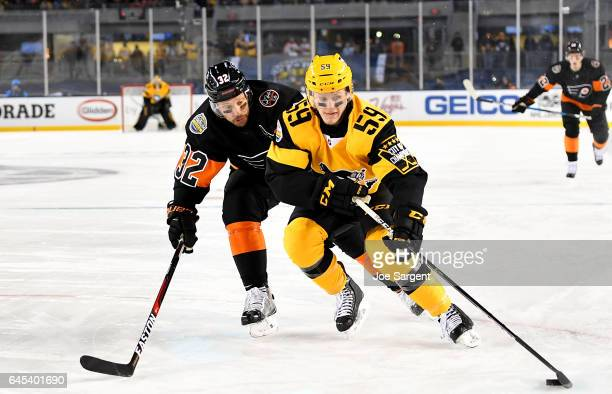 Jake Guentzel of the Pittsburgh Penguins handle the puck against Mark Streit of the Philadelphia Flyers during the 2017 Coors Light NHL Stadium...