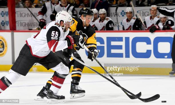 Jake Guentzel of the Pittsburgh Penguins handles the puck against Jason Demers of the Arizona Coyotes at PPG Paints Arena on November 7 2017 in...