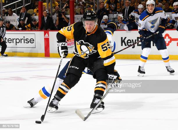 Jake Guentzel of the Pittsburgh Penguins handles the puck against the St Louis Blues at PPG Paints Arena on October 4 2017 in Pittsburgh Pennsylvania