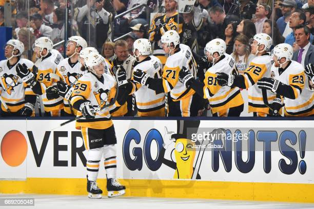 Jake Guentzel of the Pittsburgh Penguins highfives his teammates after scoring a goal during the first period in Game Three of the Eastern Conference...