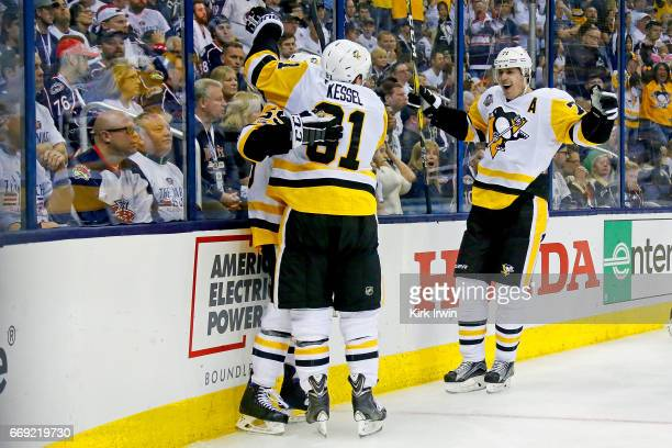 Jake Guentzel of the Pittsburgh Penguins is congratulated by Phil Kessel and Evgeni Malkin after scoring a goal during third period against the...