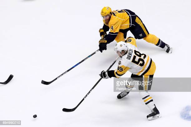 Jake Guentzel of the Pittsburgh Penguins is defended by Ryan Ellis of the Nashville Predators during the first period in Game Six of the 2017 NHL...