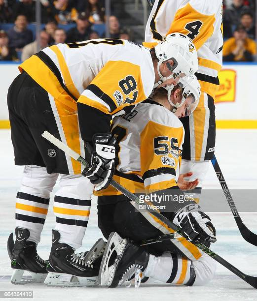 Jake Guentzel of the Pittsburgh Penguins is helped by Sidney Crosby after being injured during an NHL game against the Buffalo Sabres at the KeyBank...