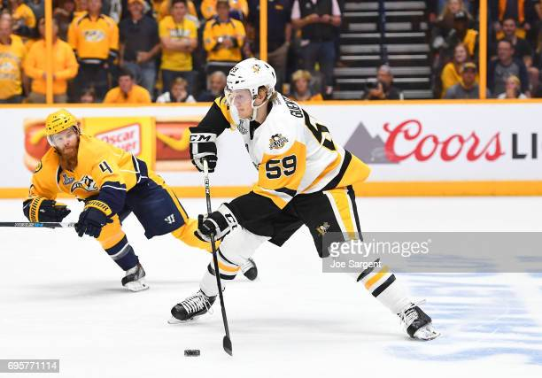 Jake Guentzel of the Pittsburgh Penguins looks to make a play with the puck as Ryan Ellis of the Nashville Predators pursues Guentzel in the first...