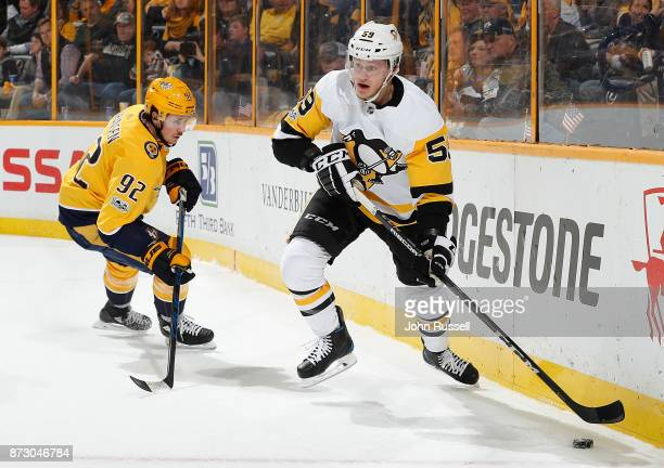 Jake Guentzel of the Pittsburgh Penguins looks to pass the puck against Ryan Johansen of the Nashville Predators during an NHL game at Bridgestone...