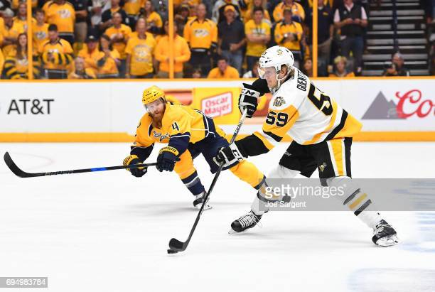Jake Guentzel of the Pittsburgh Penguins makes a pass play as Ryan Ellis of the Nashville Predators tries to get his stick in the lane in the first...
