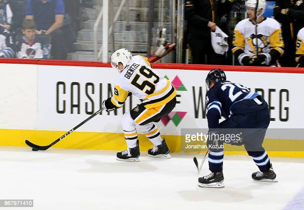 Jake Guentzel of the Pittsburgh Penguins plays the puck along the boards as Patrik Laine of the Winnipeg Jets gives chase during second period action...