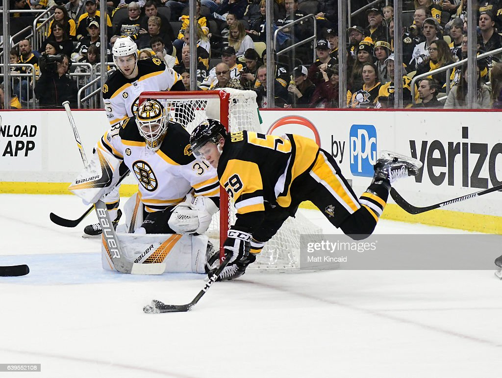 Jake Guentzel #59 of the Pittsburgh Penguins reaches for the puck as he falls to the ice against the Boston Bruins at PPG PAINTS Arena on January 22, 2017 in Pittsburgh, Pennsylvania.