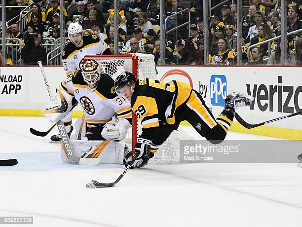 Jake Guentzel of the Pittsburgh Penguins reaches for the puck as he falls to the ice against the Boston Bruins at PPG PAINTS Arena on January 22 2017...