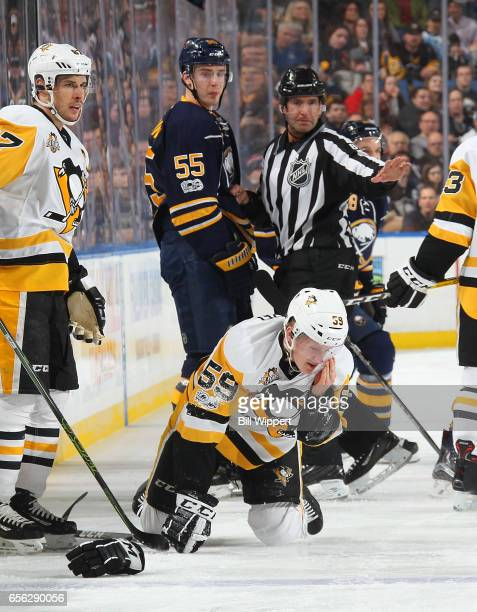 Jake Guentzel of the Pittsburgh Penguins reacts after being injured in a collision with Rasmus Ristolainen of the Buffalo Sabres during an NHL game...